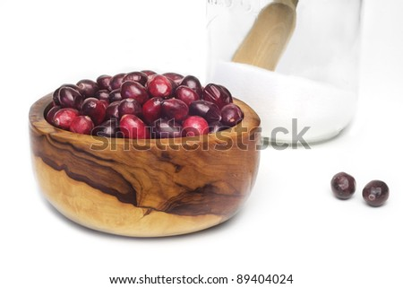 Ripe cranberries in a wooden bowl and a glass jar with sugar, isolated