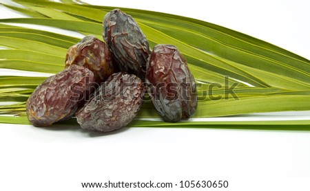 Ripe dates and leaves of palm on white background