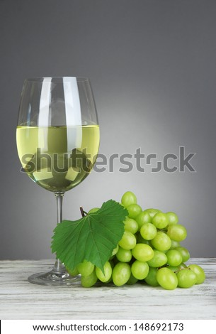 Ripe delicious grapes with glass of wine on table on gray background #148692173