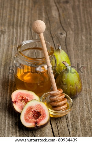 Ripe Fig Fruits with pot of honey on old wooden table