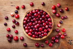 Ripe fresh cranberry in wooden bowl on rustic table top view.