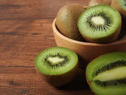Ripe fresh oval kiwifruit on a wood background. It has fibrous, bright green flesh and edible black seeds. A sweet and unique taste.It is a natural, healthy and nutritious food.With copy space.