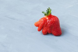 Ripe funny strawberry berry. Trendy food. Concept - Eating ugly fruits and vegetables. Space for text.