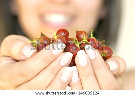 Ripe gooseberry in woman\'s hands in foreground and smiling woman face in background