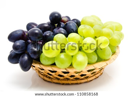 Ripe green and dark grape in the basket isolated