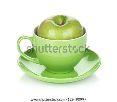 Ripe green apple in tea cup. Isolated on white background