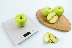 Ripe green apple on gray digital kitchen scales. On wooden board several whole apples and several sliced pieces. Healthy eating habits. Weighing products. Healthy food and diet concept.