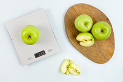 Ripe green apple on gray digital kitchen scales. On wooden board several whole apples and several sliced pieces. Healthy eating habits. Weighing products. Flat lay. Healthy food and diet concept.