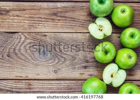 Ripe green apples and apple slices on old wooden background. Place for text. Top view