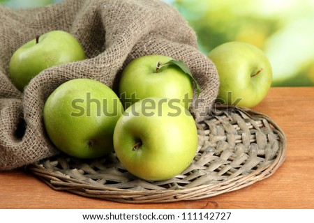 Ripe green apples with leaves on burlap, on wooden table, on green background