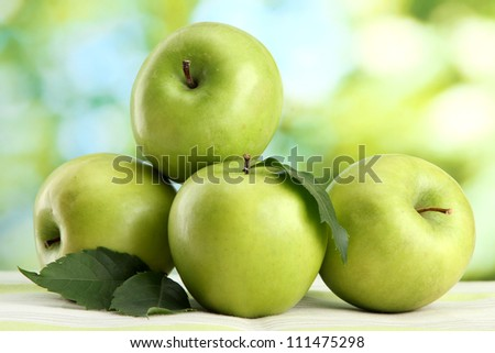 Ripe green apples with leaves, on table, on green background