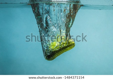 Ripe green cucumber with spray thrown into clear, clear water.