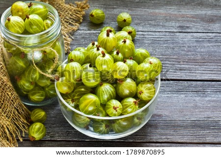 Ripe green gooseberries in a glass transparent bowl and jar on a wooden background. Harvest concept. Vegetarian food.Top view, copy space. Stock photo ©