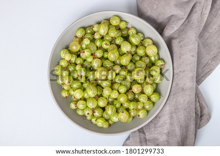 Ripe green gooseberry berry in plate bowl. Green gooseberry on light blue background. Top view Stock photo ©
