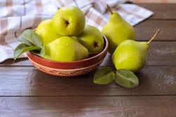 ripe green pears in a bowl on a wooden background. fresh pear closeup. background with yellow-green pears and leaves.