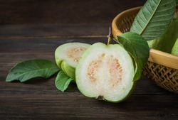 Ripe guava cut in half, four green leaves on an old wooden board.