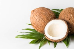 Ripe half cut coconut on a wooden background. Coconut cream and oil.
