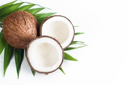 Ripe half cut coconut with green leaves on a white background. Isolated concept.