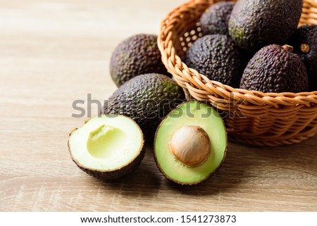 Ripe hass avocado fruit in basket on wooden background Foto stock ©