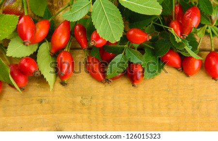 ripe hip roses on branch with leaves, on wooden background
