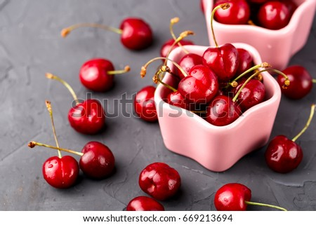 Ripe, juicy cherry in two ceramic pink bowls on the table #669213694
