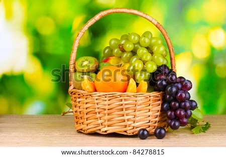 Ripe juicy fruits in basket on wooden table on green background