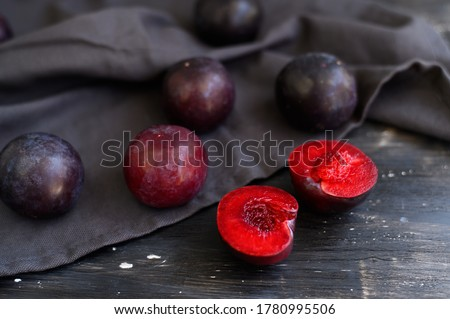 Ripe, juicy plums on a black wooden background.