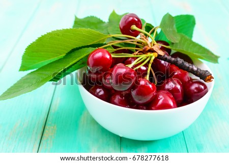 Ripe juicy red cherries in a ceramic bowl on a bright wooden background #678277618