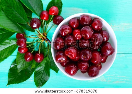 Ripe juicy red cherries in a ceramic bowl on a bright wooden background, among the leaves. Top view. #678319870