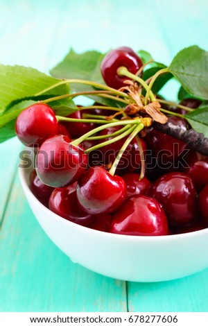 Ripe juicy red cherries in a ceramic bowl on a bright wooden background.  Vertical view #678277606