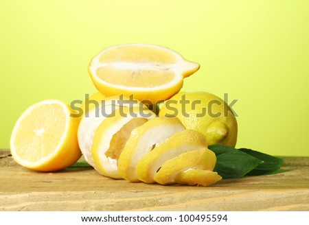 ripe lemons with leaves on wooden table on green background