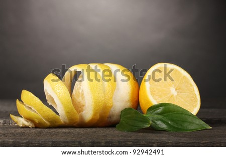 ripe lemons with leaves on wooden table on grey background