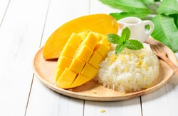 Ripe mango and sticky rice with coconut milk on white wood background, Thai dessert on summer season
