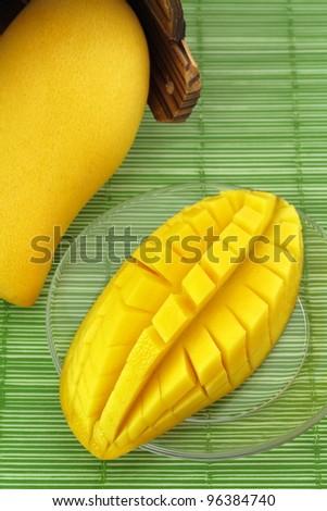 Ripe mango on a plate and put the mango wood.