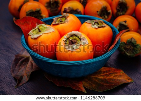 Ripe orange persimmon fruit and persimmon leaves in a blue basket on a brown wooden table