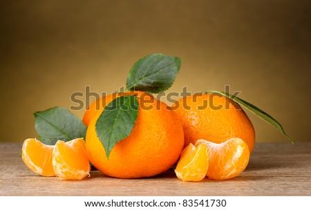 Ripe orange tangerines with segments on brown background