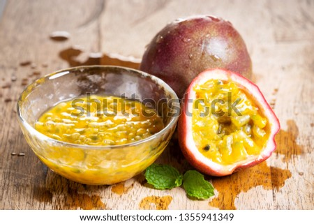 Ripe passion fruit and passion fruit juice on wooden background, closeup