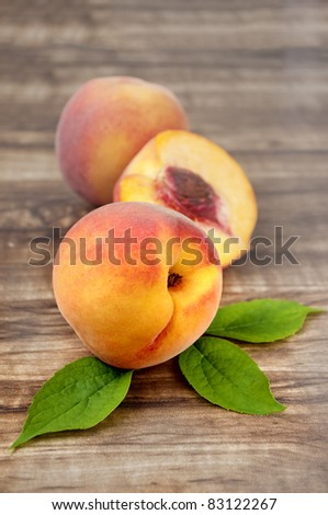 ripe peach with leaf isolated on wood  background