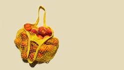 Ripe peaches in a mesh bag or string bag on light yellow background. Flat lay. Zero waste.