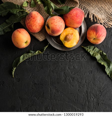 Ripe peaches on black stone background. Healthy food concept, top view, copy space