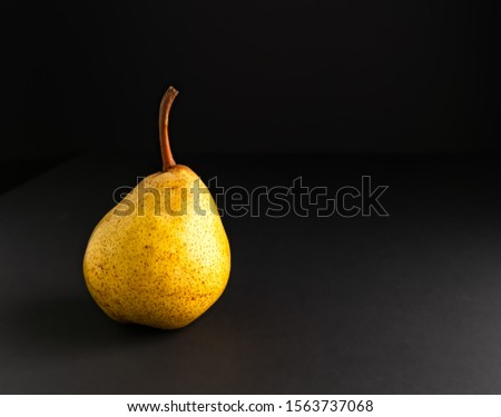 Ripe pear isolated on black background. Dark food photography with copy space.