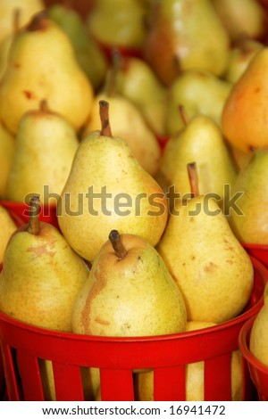 Ripe pears in red plastic baskets for sale at a fruit and vegetables open market