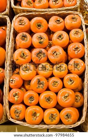 Ripe persimmon in a wattled basket