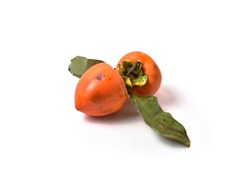 Ripe persimmon. Large orange fruits with green leaves. Pronounced structure with dark inclusions. Freshly cut from a tree. White background.