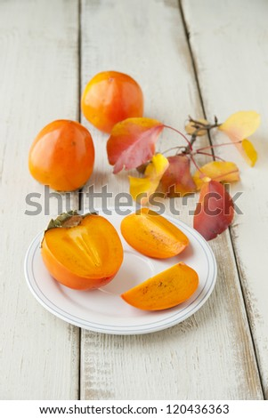 Ripe persimmon with cut on a plate, selective focus