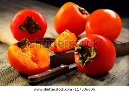 Ripe persimmons and knife on a wooden table.