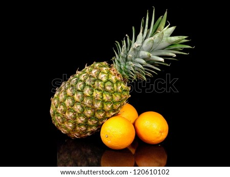 Ripe pineapple and oranges isolated on black