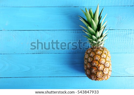 Ripe pineapple on a blue wooden table #543847933
