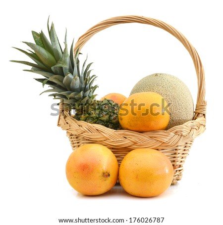 Ripe pineapple, Red Grapefruits and cantaloupe in basket. Isolated on white