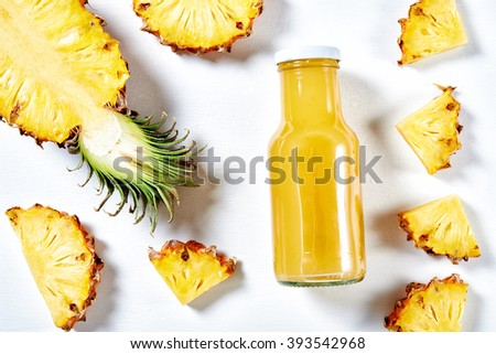 ripe pineapple slices and juice over white background. top view
